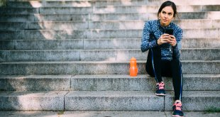 Woman dressed in sports kit with water bottle sat on steps.