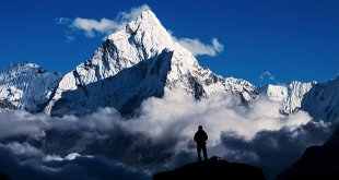 silhouette of an explorer stood in front of mountain range